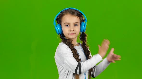 Thumbnail for Baby in the Headphones Is Listening To Music. Green Screen