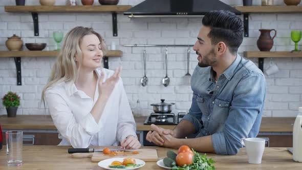 Young Smiling Interracial Couple Talking and Smiling Indoors in Kitchen