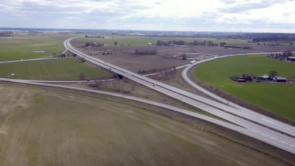 Top down aerial view of highway intersection with moving traffic cars