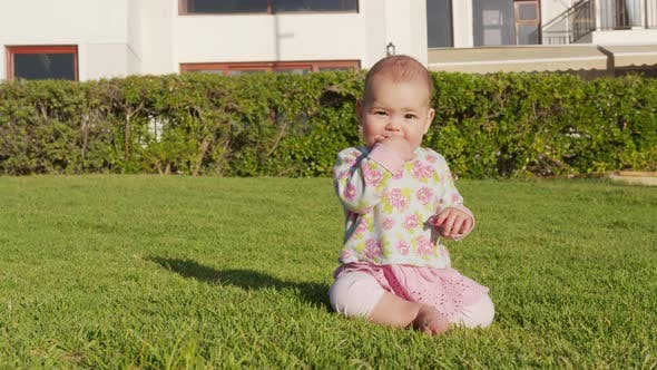 Portrait of a Little Baby Girl Playing Outdoor in the Grass