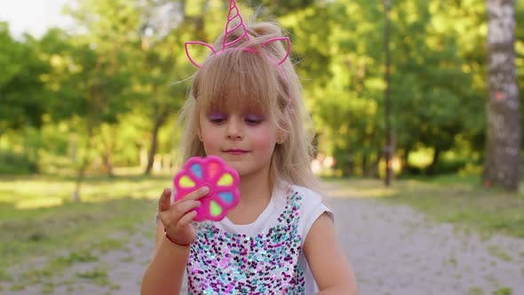 Happy Girl Playing Spinning with Pop It Sensory Antistress Toy in Park Stress Anxiety Relief