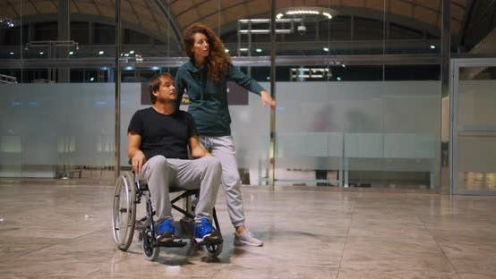 Thumbnail for Happy Disabled Man in a Wheelchair with Happy Young Woman Running at the Airport.