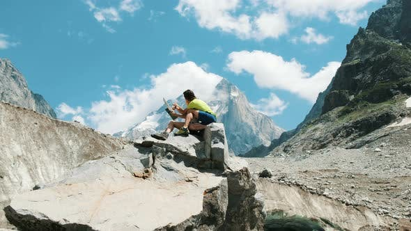 Thumbnail for Couple of Tourists Sit on a Rock and Study a Paper Map, Plan a Route in a Mountain Hike