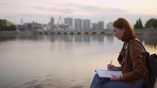 Creative Art Student Sketching Cityscape at Sunset
