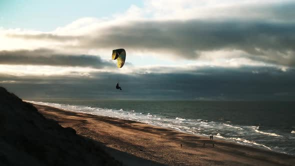 Man Paragliding Over Beach