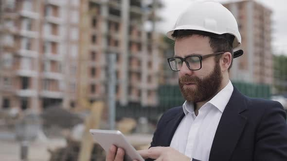 Thumbnail for Architect Man Wearing Business Suit Standing with Tablet on the Construction Site and Analyzing