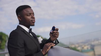 Side View of Thoughtful African American Groom in Wedding Suit Standing on Bridge Holding Wedding