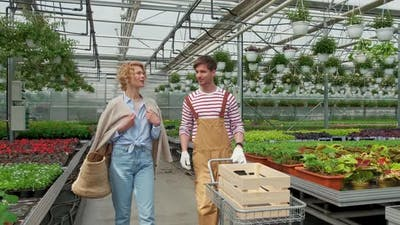 Blonde Woman Housewife Buys a Plant in the Nursery and Talks to the Gardener