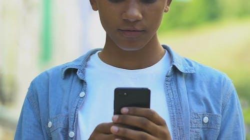 Extrem froher afroamerikanischer Junge mit Smartphone