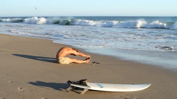 Thumbnail for A surfer stretching on the beach