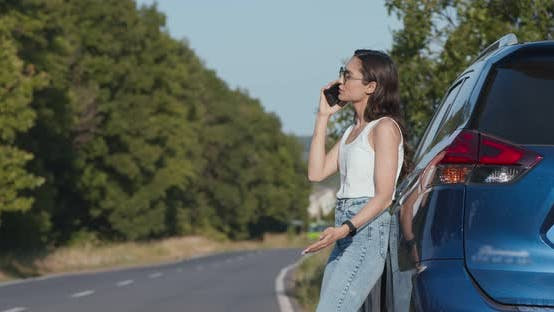 Young Frustrated Woman Talking on Mobile Phone, Leaning at Her Car with Warning Signals on