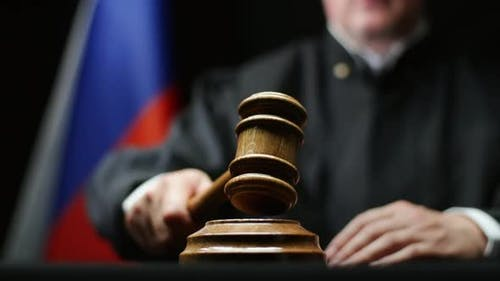 Judge With Hammer In His Hand Against Russian Flag In Court Room