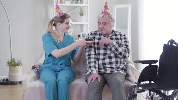 Cover Image for Kind Caucasian Woman Giving Birthday Cake To Old Grey-haired Man in Nursing Home, Depressed Retiree