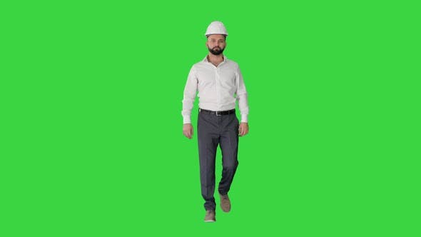 Businessman in Formal Wear and White Hardhat Walking on a Green Screen, Chroma Key.