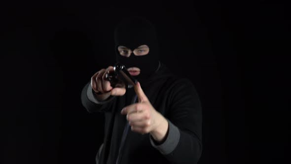 Thumbnail for A Man in a Balaclava Mask Stands with a Gun. A Thug Points His Gun at the Camera. On a Black