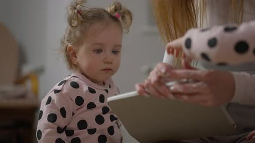 Portrait of Cute Curious Baby Girl Watching at Unrecognizable Woman Surfing Internet on Tablet