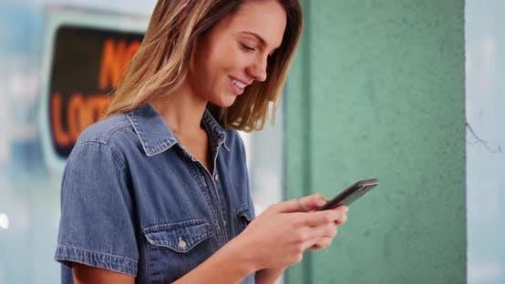 Thumbnail for Nahaufnahme der attraktiven Millennial Mädchen SMS auf Handy außerhalb Gebäude