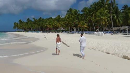 Couple in Love is Walking on a Tropical Beach Foamy Blue Ocean Waves Vacation