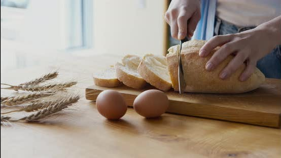 Woman Cutting Crispy Loaf of Bread on Rustic Table
