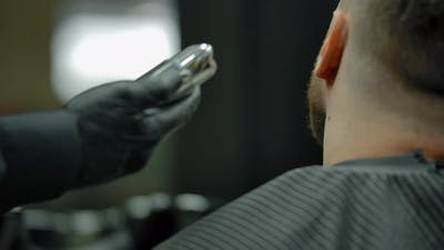 Unrecognizable Man Shaving Customer Beard with a Trimmer