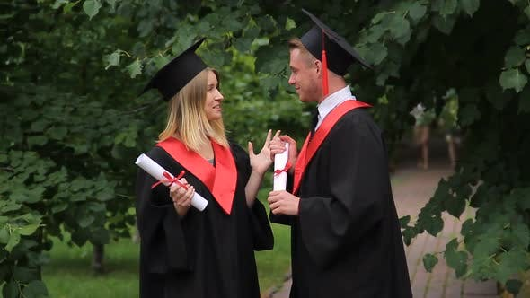 Thumbnail for Happy Male and Female Graduates Chatting About Future in Park, Graduation Day