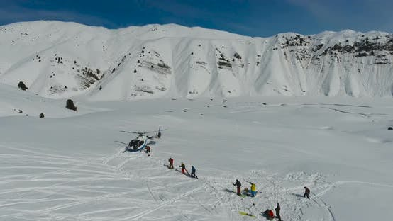 Cover Image for Skiers and snowboarders board a Helicopter in the winter mountains