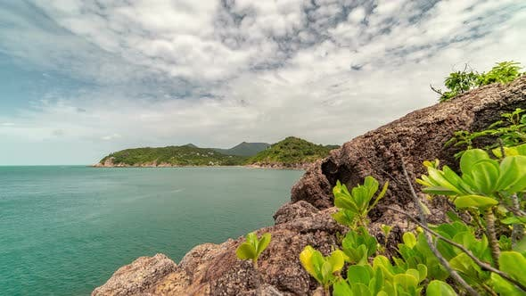 Cover Image for Tropical plants on a rocky coast in the background of the sea and islands Koh Phangan, Thailand