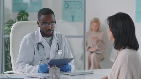 Afro-American Doctor Giving Medical Consultation to Woman
