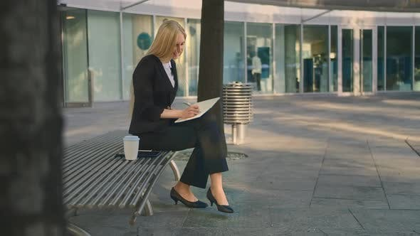 Thumbnail for Successful Business Woman Taking Notes Outdoors. Side View of Elegant Girl Sitting on Bench in Patio