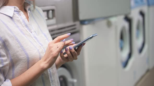 A Woman in a Public Laundry Holds a Smartphone in Her Hand and Conducts Correspondence While Washing