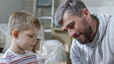 Proud Father Praising Son for Assembling Shelf