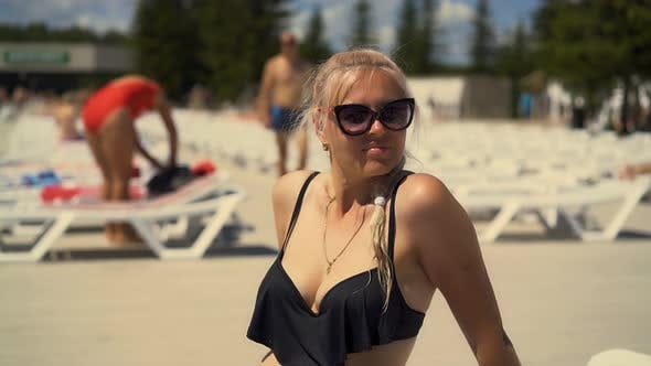 Closeup Blonde Girl Is Sitting on Deck Chair on the Beach in Sunglasses Her Hair Is Braided in a