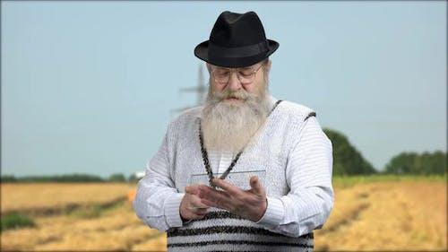 Senior Farmer Working on Futuristic Tablet Pc