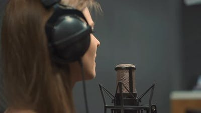 Vocalist Sings Song with Microphone in Recording Studio
