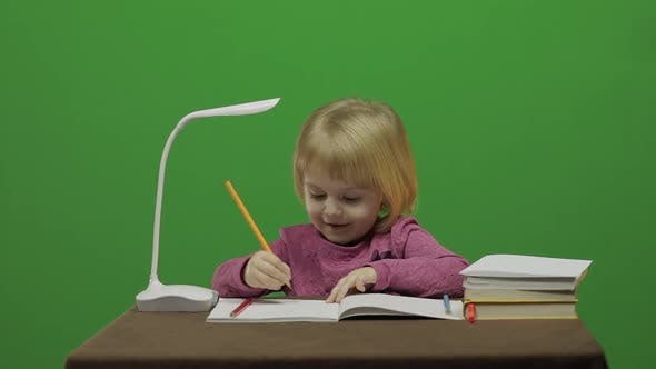 Girl Drawing at the Table. Education Process in Classroom. Chroma Key