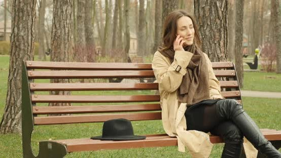 Thumbnail for Beautiful girl talking on phone sitting on bench in autumn park smiling and enjoying conversation