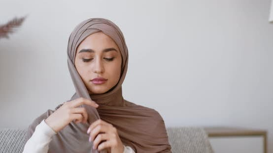 Thumbnail for Islamic Traditional Headwear. Young Muslim Woman Putting on Hijab, Sitting on Couch at Home