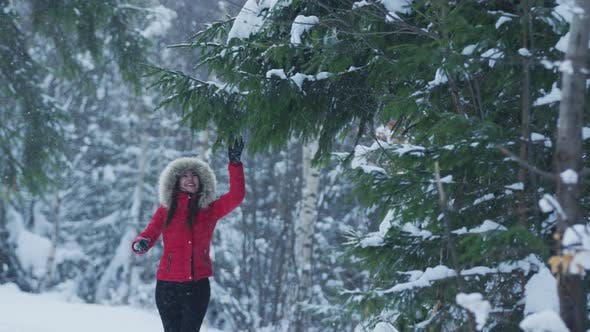 Girl playing with a snowy branch
