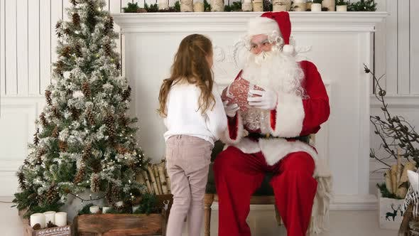 Thumbnail for Little Girl Presenting Santa Claus with Christmas Gift