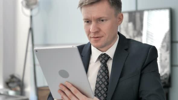 Thumbnail for Businessman Celebrating Success on Tablet