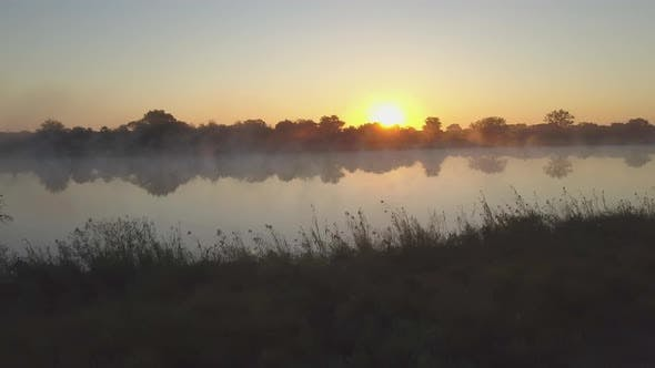 Thumbnail for Aerial drone view of a sunset sunrise over a lake with fog in Africa