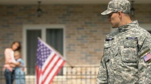 Sad Serviceman Leaving House Looking Wife and Daughter Hugging Background, Duty