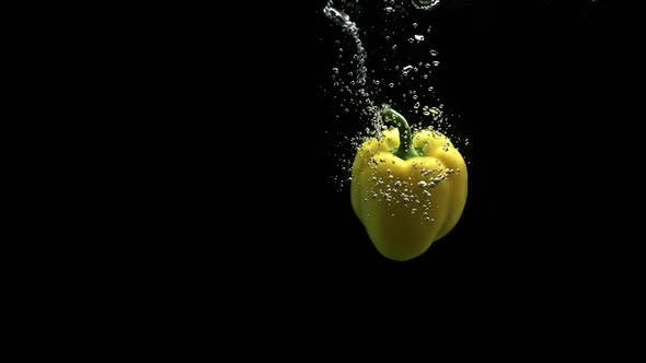 Thumbnail for Yellow Bell Pepper Falling In Clean Water And Spinning With Lot Of Air Bubbles Black Background
