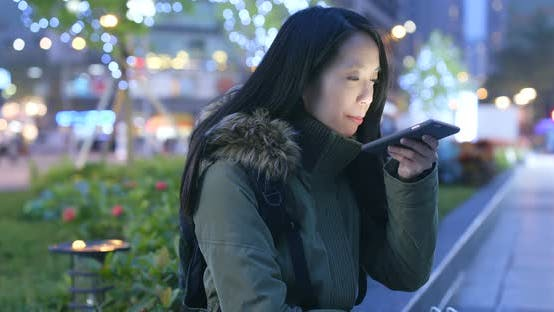 Cover Image for Woman using mobile phone in the city at night