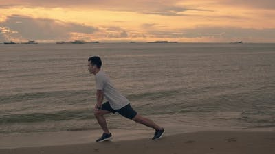 A handsome Asian sportsman stretching exercises before running exercise outside.