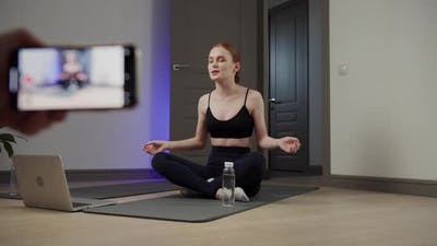 Girl Athlete Writes a Video Blog on the Phone and Meditates