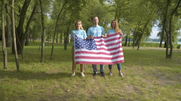 Thumbnail for Group of Smiling Volunteers Posing with American Flag on Sunny Day After Cleaning Park, Portrait