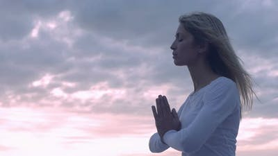 young woman in meditation near the sea: practicing yoga
