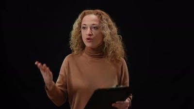 Emotional Caucasian Woman Talking Gesturing Standing at Black Background