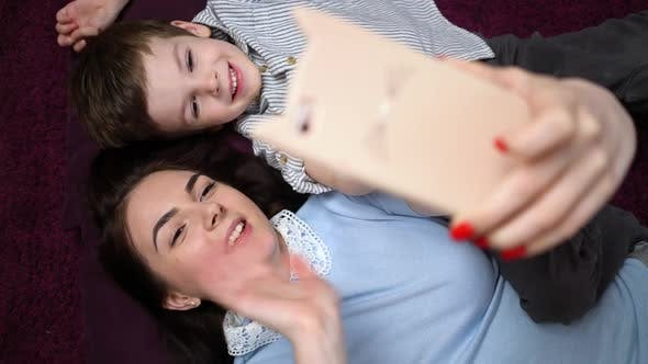 Mother and Her Son Making a Selfie or Video Call To Father or Relatives on the Carpet.